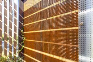 Perimeter of garden, perforated oxidized metal screens