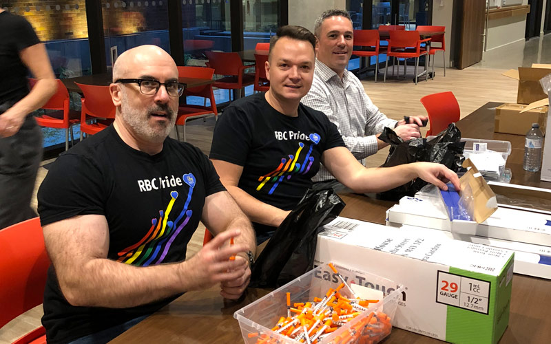 Photo of volunteers from RBC building harm reduction kits for distribution. The photo was taken pre-COVID in 2018.