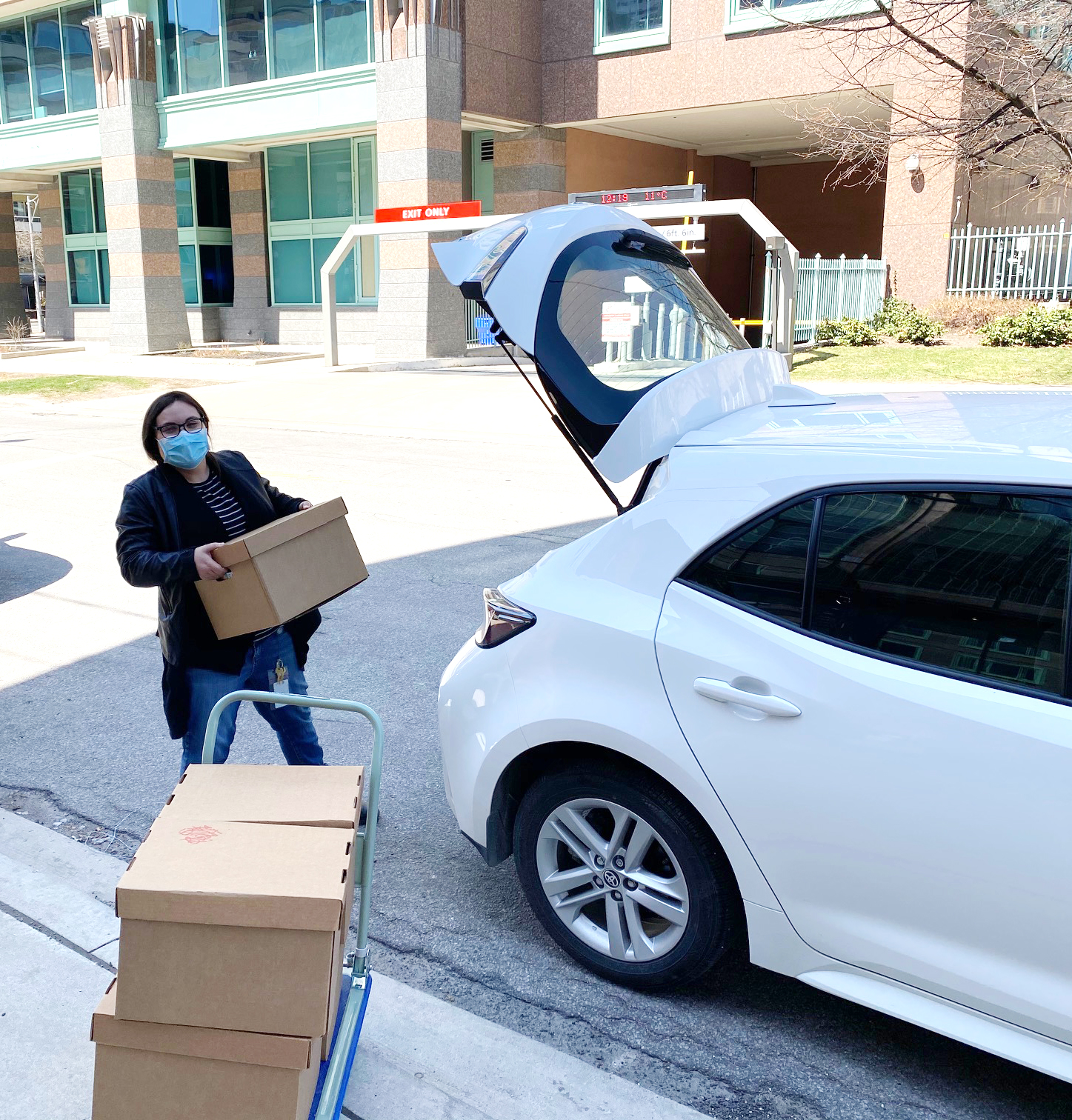 Woman wearing a mask and a toque loading a box of food into a white hatchback