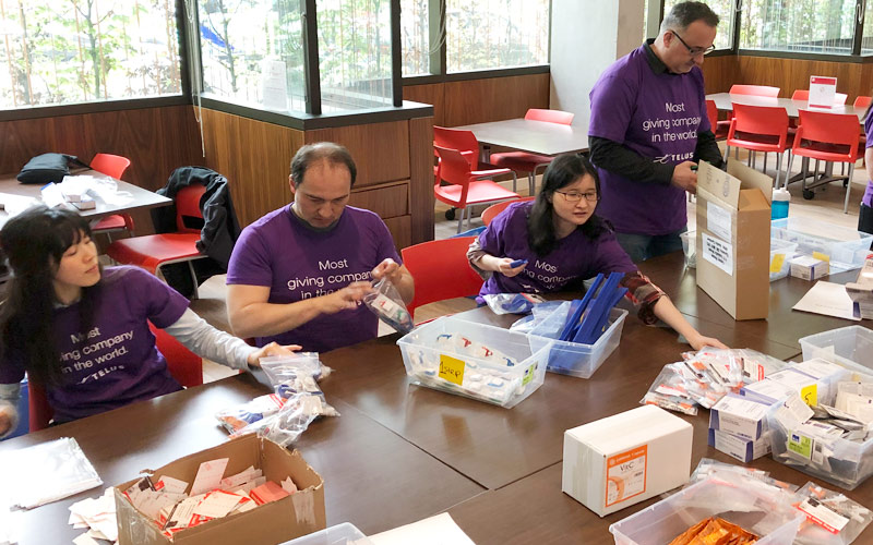Volunteers from Telus building harm reduction kits for distribution. This photo was taken pre-COVID-19 in 2019